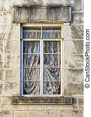 Weathered Window in a Limestone Wall - Old metal-framed,...