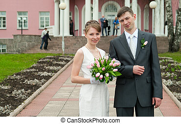 Young loving wedding couple with bunch of flowers Newlywed...