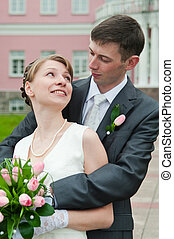 Young loving wedding couple with bunch of flowers. Newlywed pair
