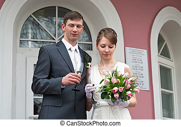 Bride and groom standing near registry office with glasses of champagne. Caucasians. Young wedding couple