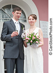 Bride and groom standing near registry office with glasses...