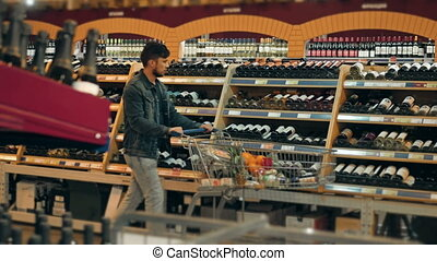 Young Man Chooses Bottle of Wine In The Supermarket, 4K, UHD