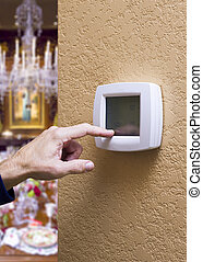 Touchpad Thermostat in an Elegant Home - Closeup of a male...