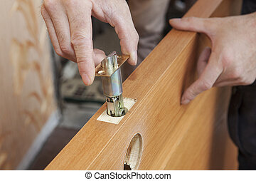 Close-up carpenter hands door lock installation. -...