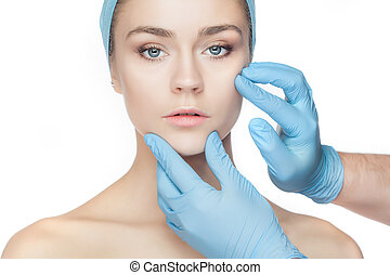 Plastic surgery concept. Doctor hands in gloves touching...