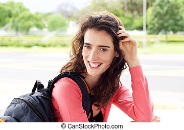 Smiling young female traveler woman with backpack