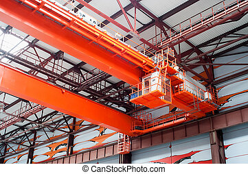 Large-tonnage industrial orange Goliath crane loading of goods in factory mill