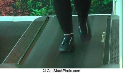 Woman on racetrack simulator Feet view - Woman does exercise...