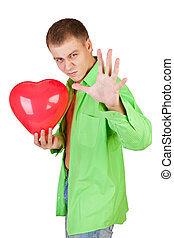 portrait of a smiling young man holding a red heart shaped...