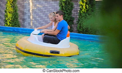 Couple floating around inside electric rubber boat HD