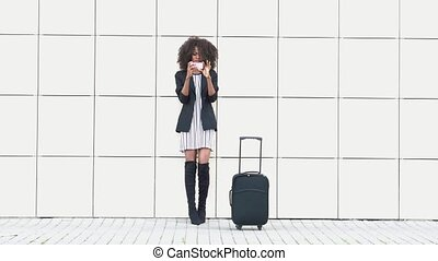 Elegant slim african american woman with luggage makes selfie at the airport. White textured wall background. Getting ready for voyage