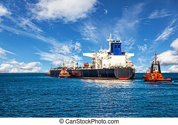 Ship with Tugboats - Tugboats towing a tanker ship at sea