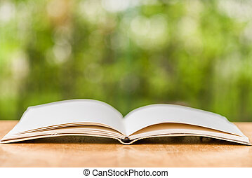 Opening book on the table with nature background