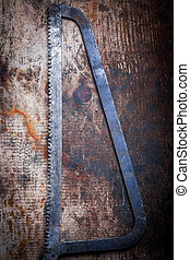 Hacksaw on wooden plank - Color image of a hacksaw on a...