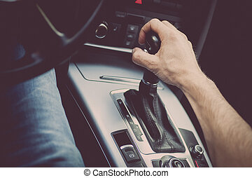Hand on gear stick - Detail of a hand pulling an automatic...