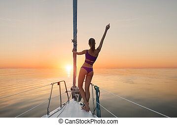 Girl standing on yacht bow.