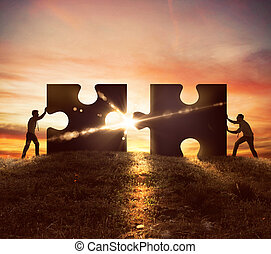 Cooperation at work - Men push two puzzle pieces at sunset