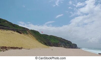 Paragliders Fly Over the Ocean Beach, sunny day