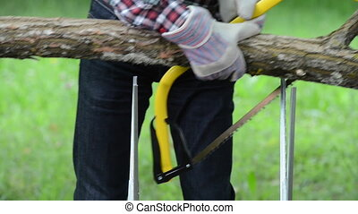 Senior man sawing a log handsaw closeup - Senior man sawing...
