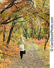 Lonely woman in a bright autumn forest Rear view