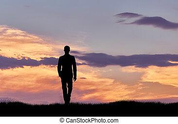 Silhouette of man walking at sunset