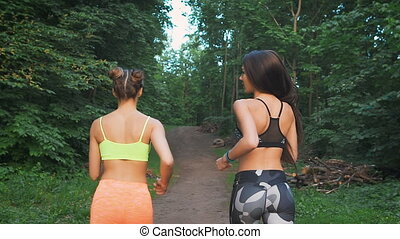 Two fitness girls running through the woods They practice...