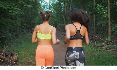 Two fitness girls running through the woods. They practice sport life style. For the health and tone.
