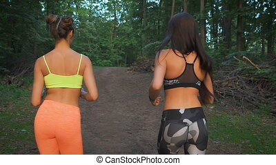 Two fitness girls running through the woods. They practice...