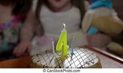 Girl claps and blows out candles on birthday cake - Little...