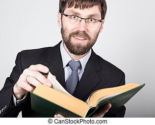 bearded businessman in a business suit and tie, reading a thick book