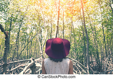 Woman with red hat in forest.