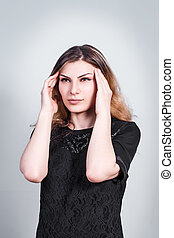 Young beautiful woman with headache on gray background