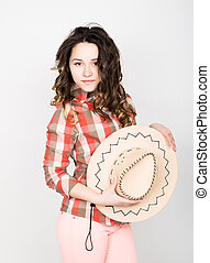 beautiful curly girl in pink pants, a plaid shirt and cowboy...