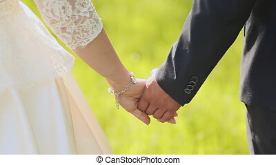 Young married couple holding hands, ceremony wedding day.