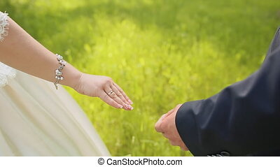 The bride and groom take each others hands and go