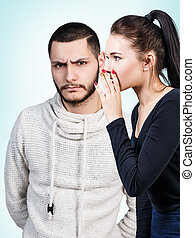 Girl whispering secret to young man - Young girl whispering...