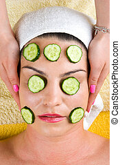 Woman with cucumber slice facial mask at spa - Beautician...