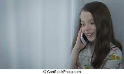 Beautiful little girl emotional talking on smart phone by...