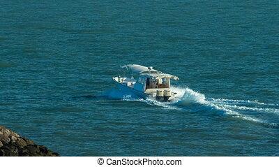Motor boat moving from harbor to Gulf near the Sharq Marina...