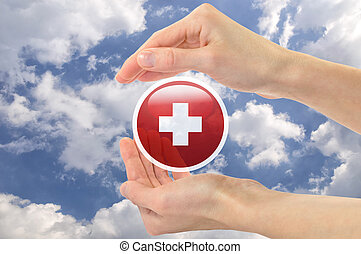 Red cross symbol in human hands against the sky - Concept of...