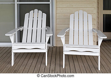Two white wooden adirondack chair on old weathered front...