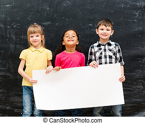 three cute children holding an empty paper sheet for ad with...