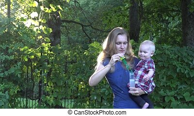mother woman blow soap bubbles with curious baby on hands on...