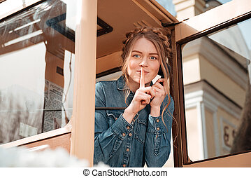 Happy woman calling from telephone box and showing silence...