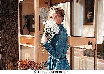 Woman with bicycle and bouquet of camomiles standing on...