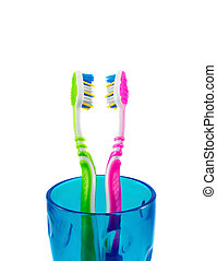 Two toothbrushes in a blue cup