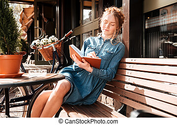 Relaxed woman sitting on bench and writing in notebook -...