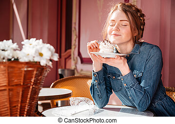 Happy woman eating sweet tasty cupcake in outdoor cafe -...