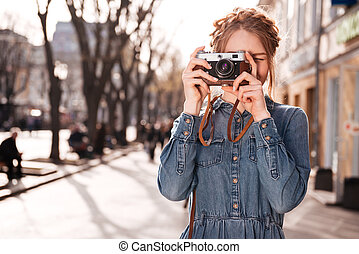Concentrated woman taking pictures outdoors using old...