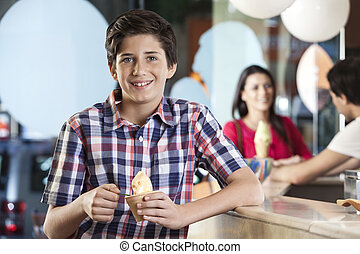 Smiling Boy Having Ice Cream At Parlor - Portrait of smiling...
